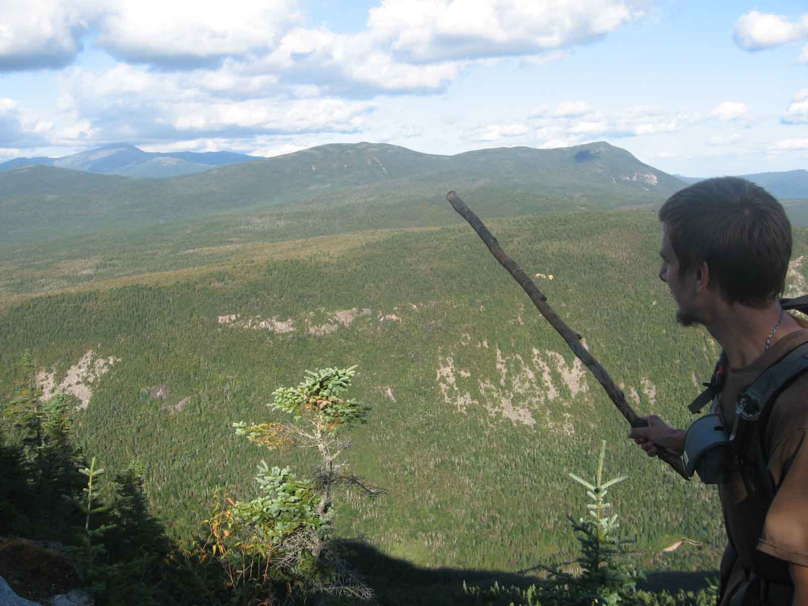 Turok pointing out Mount Washington in the distance with his hiking stick.